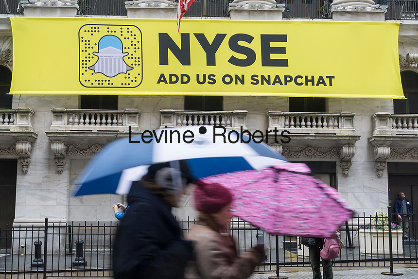 Tourists and workers pass the front of the New York Stock Exchange, decorated with a sign promoting Snapchat, on Tuesday, January 24, 2017. Snap Inc. is planning an initial public offering this year, possibly valuing the company at at least $25 billion. The NYSE and Nasdaq are both competing for the IPO. (© Richard B. Levine)