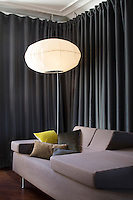 In the living room curtains are used to partition the space; the sofa bed is a design by Gregoire de Lafforest and the standard lamp is an inflatable design by Eric Jourdan
