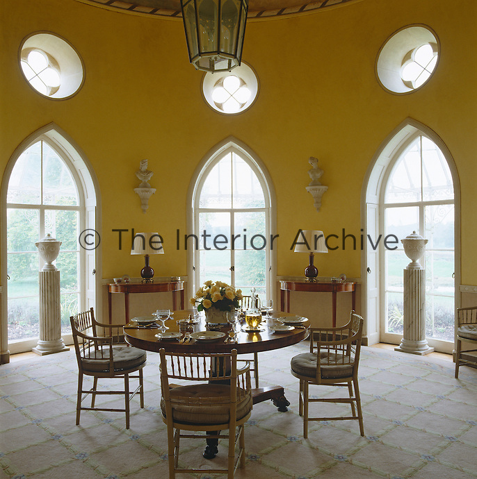 A small round table laid for lunch in a circular room with three gothic windows