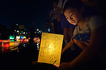 A girl sets a floating candle lantern on the river on August 6, 2015, in Hiroshima, Japan. The lanterns, thousands of which were launched on the 70th anniversary of the atomic bombing of the city, carried handmade messages and drawings, conveying each person's prayers for peace and comfort for the victims of the violence.