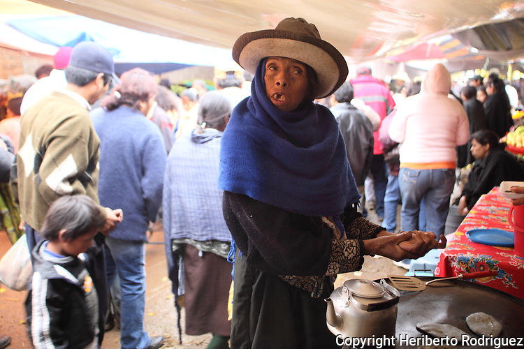An old Native nahuatl woman warms her hands as she buys ofrenda stuff in the tianguis in Acaxochitlan, in northern state of Hidalgo, during the festivities of the Day of the Deads. Hundreds of Native villages pay homage to their deads on the eve of November 2 as a tradition since the preHispanic times. Photo by Heriberto Rodriguez