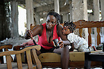 """Wedlin Victor paints furniture in her family's carpentry shop in Gressier, Haiti, as her 8-month old daughter Rose Marie looks on. They live in a model resettlement village constructed by the Lutheran World Federation in Gressier. The settlement houses 150 families who were left homeless by the 2010 earthquake, and represents an intentional effort to """"build back better,"""" creating a sustainable and democratic community."""