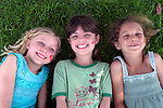 Three 6-year-old girls smile and laugh and enjoy the shade and grass on a summer's day.