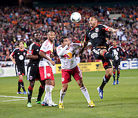 Kyle Porter (19) of D.C. United heads the ball away from Tim Cahill (17) of New York Red Bulls during the game at RFK Stadium in Washington, DC.  New York Red Bulls defeated D.C. United, 2-0.