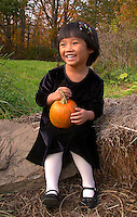 Asian American Girl holding pumpkin and smiling all dressed up