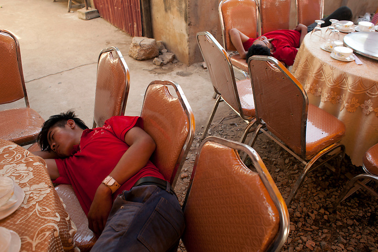 Caterering staff fall asleep before a buddhist wedding in a small village outside of Phnom Penh, Cambodia. <br /> <br /> Photos &copy; Dennis Drenner 2013.