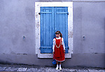 Little girl in a red dress stands against a wall with a blue-shuttered window in France.