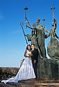 Couple posing for wedding photos at La Rogativa sculpture in Old San Juan, Puerto Rico.