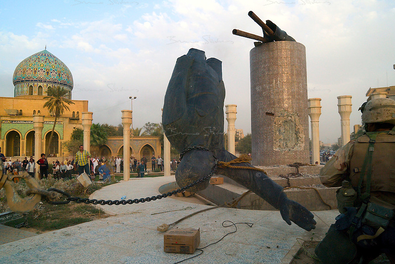 Baghdad, Iraq, April 9, 2003.A jubilant crowd watches as a monumental statue of Saddam is toppled by a US Marine crane.