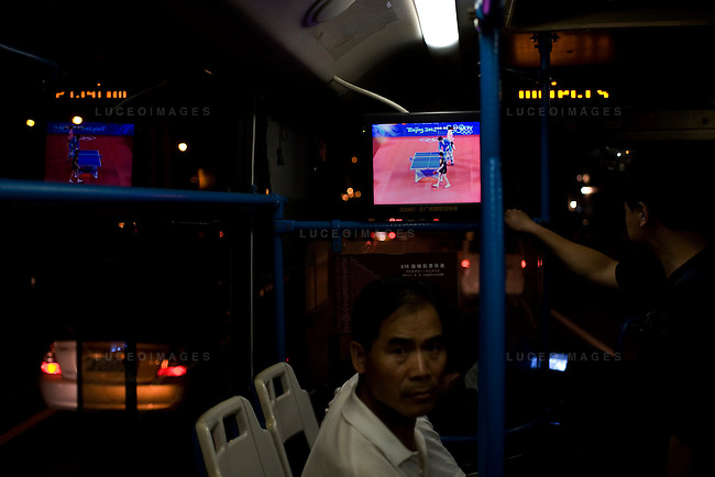 Locals watch an Olympic ping pong match while riding the city bus home in Beijing, China on Friday, August 22, 2008.  Kevin German