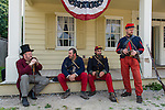 "Old Bethpage, New York, USA. August 30, 2015. L-R in soldier uniforms, SEAN SULLIVAN from Greenlawn, ANDRES PREBLE from Long Beach, and MATT DELLINGER from Brooklyn, portray American Civil War soldiers from the 14th Brooklyn Regiment (14th New York State Militia) AKA The Brooklyn Chasseurs, at the Noon Inn tavern during the Old Time Music Weekend at the Old Bethpage Village Restoration. During their historical reenactments, m embers of the non-profit 14th Brooklyn Company E wear accurate reproductions of ""The ""Red Legged Devils"" original Union army uniform."