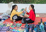 Two young girl vendors on the street in Luang Prabang take a break from selling and play the same hand game that young girls play around the world.