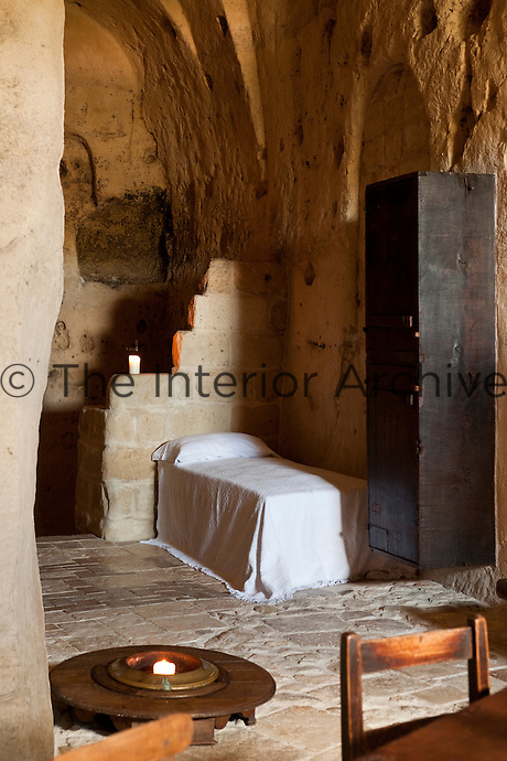 A day bed has been cleverly placed in the corner of this bedroom at the unique Albergo Diffuso Le Grotte della Civita in Southern Italy housed in restored caves