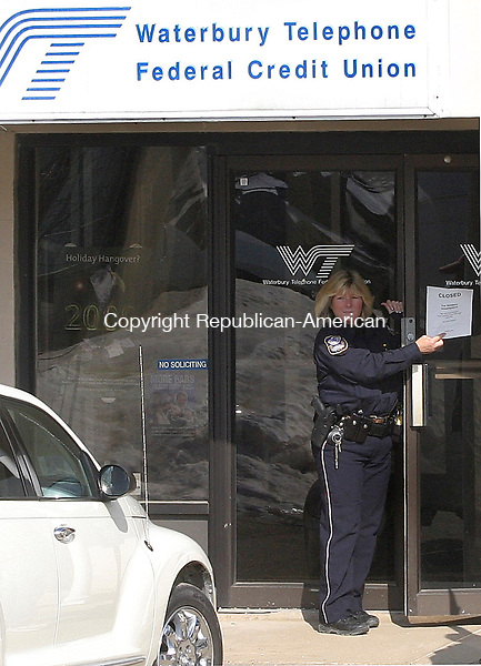 WATERBURY,CT-06 FEBUARY 07_NEW_020609DA01.jpg-  Waterbury Police Officer Soden shows a closed sign to a customer of the Waterbury Telephone Federal Credit Union while the bank was being investigated after a robbery Friday afternoon.<br />  Darlene Douty