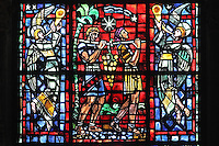 The grapes of the promised land, men carrying a harvest of grapes with angels playing trumpets, lancet window from the South transept, by Jacques Simon, commissioned in 1954 by the Corporation des Vins de Champagne, the lobby of Champagne producers, after damage to the original windows in WWII, in the Cathedrale Notre-Dame de Reims or Reims Cathedral, Reims, Champagne-Ardenne, France. The cathedral was built 1211-75 in French Gothic style with work continuing into the 14th century, and was listed as a UNESCO World Heritage Site in 1991. Picture by Manuel Cohen
