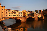 Oblique view of the Ponte Vecchio, Florence, Tuscany, Italy, pictured on June 8, 2007, in the evening. The Ponte Vecchio, or Old Bridge, crosses the River Arno at its narrowest point. The original bridge, possibly Roman and first documented in 999, was swept away in a flood in 1117, rebuilt, swept away again in 1333 and rebuilt in 1345. In 1565 Cosimo de Medici commissioned Vasari to design a corridor, above the famous shops along the bridge, connecting the Palazzo Vecchio to the Pitti Palace. In 1593 the Medicis prohibited butchers, the traditional occupants, from the shops which were soon taken by Goldsmiths. Florence, capital of Tuscany, is world famous for its Renaissance art and architecture. Its historical centre was declared a UNESCO World Heritage Site in 1982. Picture by Manuel Cohen.