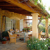 A simple lunch is laid on the painted table of this sheltered terrace overlooking the garden