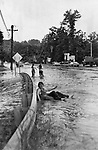 knee-deep water from Bullet Hill Brook swirled across Route 67 in Southbury during the flood of 1973. Tom Kennessy decided to ride our the flood on an inner tube.