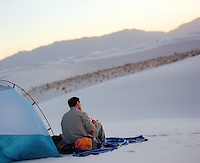 Man writing while seated outside his tent during a sunset in White Sands National Park, NM