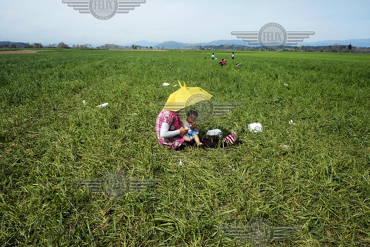 A refugee woman shields her child from the sun with an umbrella as they rest in farmer's field near the makeshift refugee camp at Idomeni. Around 14,000 people were stranded in the camp which the authorities have since closed and distributed the occupants among several official camps around the country.