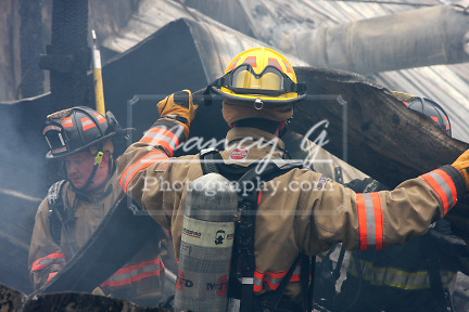 Firefighters removing debris from a collapsed building from a fire