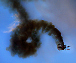 The oracle biplane cruises through its maneuvers trailing smoke during a Rose Festival Air Show twilight performance at Hillsboro Airport.