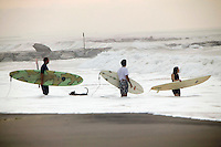 Surfers prepare to enter the water at Far Rockaway beach in New York, United States, in the early morning of 17 September 2005. Photo Credit: David Brabyn.