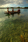 Children on a outrigger canoe in the village of Hessessai Bay at PanaTinai (Panatinane)island in the Louisiade Archipelago in Milne Bay Province, Papua New Guinea.  The island has an area of 78 km2..The Louisiade Archipelago is a string of ten larger volcanic islands frequently fringed by coral reefs, and 90 smaller coral islands located 200 km southeast of New Guinea, stretching over more than 160 km and spread over an ocean area of 26,000 km? between the Solomon Sea to the north and the Coral Sea to the south. The aggregate land area of the islands is about 1,790 km? (690 square miles), with Vanatinai (formerly Sudest or Tagula as named by European claimants on Western maps) being the largest..Sideia Island and Basilaki Island lie closest to New Guinea, while Misima, Vanatinai, and Rossel islands lie further east..The archipelago is divided into the Local Level Government (LLG) areas Louisiade Rural (western part, with Misima), and Yaleyamba (western part, with Rossell and Tagula islands. The LLG areas are part of Samarai-Murua District district of Milne Bay. The seat of the Louisiade Rural LLG is Bwagaoia on Misima Island, the population center of the archipelago.PanaTinai (Panatinane) is an island in the Louisiade Archipelago in Milne Bay Province, Papua New Guinea. The island has an area of 78 km2..The Louisiade Archipelago is a string of ten larger volcanic islands frequently fringed by coral reefs, and 90 smaller coral islands located 200 km southeast of New Guinea, stretching over more than 160 km and spread over an ocean area of 26,000 km? between the Solomon Sea to the north and the Coral Sea to the south. The aggregate land area of the islands is about 1,790 km? (690 square miles), with Vanatinai (formerly Sudest or Tagula as named by European claimants on Western maps) being the largest..Sideia Island and Basilaki Island lie closest to New Guinea, while Misima, Vanatinai, and Rossel islands lie further east..The archipelago is divided into the Local Leve