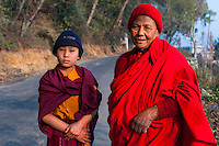 A buddhist nun and young scholar of Buddhism on their way to a sacred cave where they conduct a daily prayer and devotional ceremony.