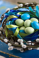 A still-life of blue and green Easter eggs in a nest made of pussy willow stems