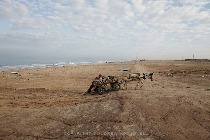 A man pushes his rubble laden cart up a hill on Gaza's coast, near the northern border with Israel.