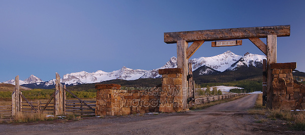 Ranch gate Uncompahgre Mountains and Aspen trees in fallcolor at dusk, Last Dollar Ranch, Rocky Mountains, Colorado, USA, September 2006