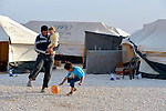 A man plays football with his children--one in his arms--in the Zaatari Refugee Camp, located near Mafraq, Jordan. Opened in July, 2012, the camp holds upwards of 50,000 refugees from the civil war inside Syria. International Orthodox Christian Charities and other members of the ACT Alliance are active in the camp providing essential items and services.