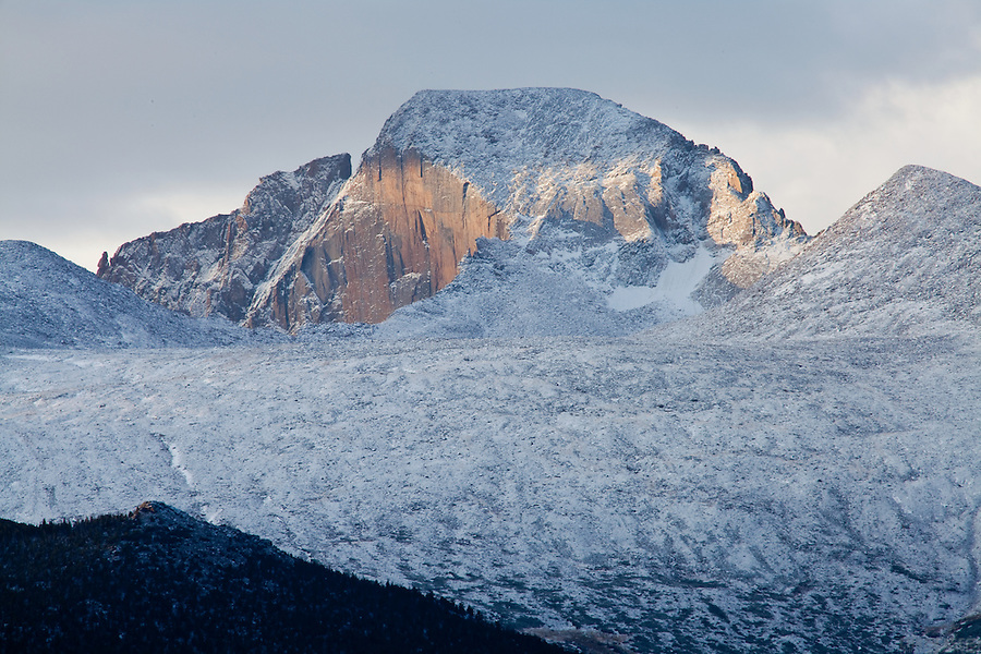 A rising sun glints off of the Diamond Wall after an autumn snowfall on Longs Peak in Rocky Mountain National Park, Colorado.