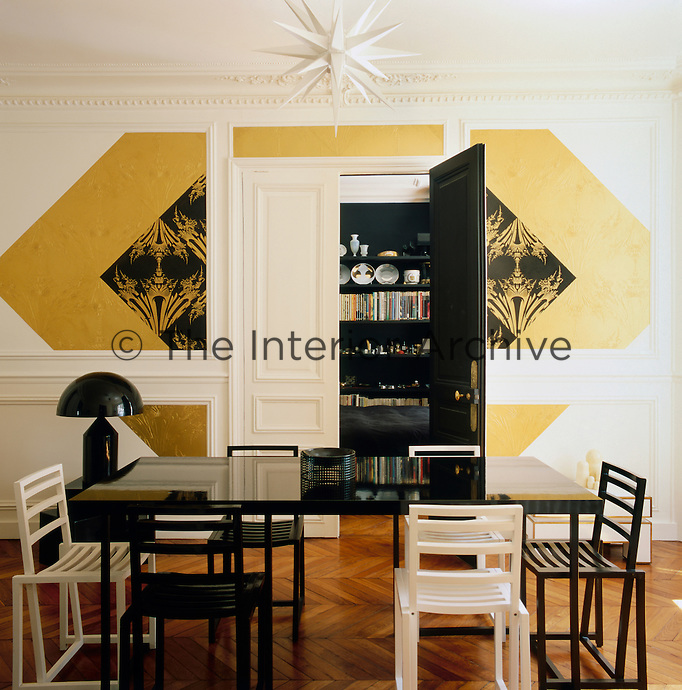 Graphic patterns, added to a simple palette of white, black and gold create an elegant combination, whilst the contemporary furniture contrasts with the original period features in this Paris apartment. The dining room is spacious and minimal with simple furniture. The double doors give access to the bedroom