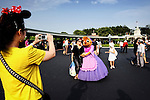 Tourists from China take each other's photos with Cinderella characters Suzy and Perla at Tokyo Disneyland in Chiba, Japan.