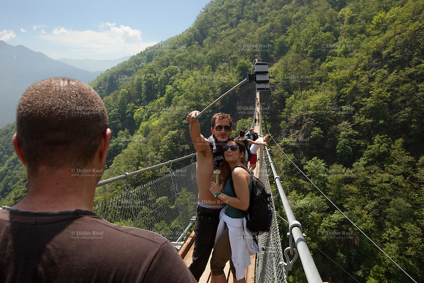 "Switzerland. Canton Ticino. Sementina valley. ""Caracs"" Tibetan bridge. A young loving couple takes a selfie on the bridge with an iPhone and a stick. The 270 m long Tibetan bridge build by the Foundation Curzútt-S. Barnard allows the passage of the rugged valley that separates the communities of Sementina and Monte Carasso, two towns located in front of Bellinzona. The bridge joins the stone made village of Curzútt to the hiking path of ""Via delle Vigne"", allowing people to make excursions in an area characterized by a landscape rich in cultural heritages. Anchored at a height of 696 m, the bridge rises 130 m above the ground. The walkway, large approximatively one meter, is made of larch wood. Crossing it is a unique experience that represents a true challenge. The safety measures guarantees a risk-free approach and make it a top-attractions either for young intrepid or adventurous families. 14.05.2015 © 2015 Didier Ruef"