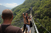 """Switzerland. Canton Ticino. Sementina valley. """"Caracs"""" Tibetan bridge. A young loving couple takes a selfie on the bridge with an iPhone and a stick. The 270 m long Tibetan bridge build by the Foundation Curzútt-S. Barnard allows the passage of the rugged valley that separates the communities of Sementina and Monte Carasso, two towns located in front of Bellinzona. The bridge joins the stone made village of Curzútt to the hiking path of """"Via delle Vigne"""", allowing people to make excursions in an area characterized by a landscape rich in cultural heritages. Anchored at a height of 696 m, the bridge rises 130 m above the ground. The walkway, large approximatively one meter, is made of larch wood. Crossing it is a unique experience that represents a true challenge. The safety measures guarantees a risk-free approach and make it a top-attractions either for young intrepid or adventurous families. 14.05.2015 © 2015 Didier Ruef"""