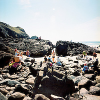 Families relax on a beach on a sunny day at Kynance Cove in Cornwall.