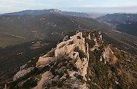 "Lower Castle seen from High Castle, Peyrepertuse Castle or Chateau Pierre Pertuse, Cathar Castle, Duilhac-sous-Peyrepertuse, Corbieres, Aude, France. This castle consists of a Lower Castle built by the Kings of Aragon in the 11th century and a High Castle built by Louis IX in the 13th century, joined by a huge staircase. Its name means pierced rock in Occitan and it has been associated with the Counts of Narbonne and Barcelona. It is one of the ""Five Sons of Carcassonne"" or ""cinq fils de Carcassonne"" and is a listed monument historique. View shows hilltop location and Pyrenees surrounding site. Picture by Manuel Cohen"
