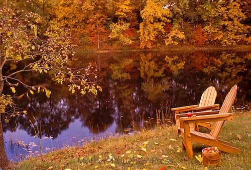 Two Adirondack chairs sit beside fall lake  with antique bucket of apples and nets to be peeled