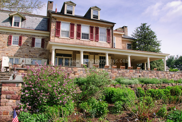 Fordhook Farm historic register house in May spring with lilac bush Syringa, porch with columns, retaining wall, perennial beds