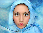 The face of a beautiful young woman framed in blue fabric