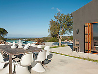 The large concrete terrace surrounding the house is separated into areas for relaxing/sunbathing around the pool and dining