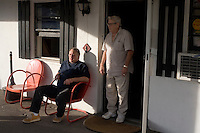 "Joel Dubeshter (left) and Art Love hang out outside the lobby of Motel Caswell in Tewksbury, Massachusetts, USA, on Tuesday, Oct. 11, 2011.  Dubeshter, 58, has lived at Motel Caswell ""on and off for 3 years.""  Art Love has worked in the motel's office for 6 years. Dubeshter says, ""This [place] is a stepping stone."" His mail is delivered to the motel and he's moved in some of his own furniture, including a walnut dresser previously owned by his parents, and keeps the room clean on his own instead of relying on the motel's maids. Dubeshter previously worked for the Boston Globe in the mail room where he served as union chairman for a time, but the job took its toll after nearly 30 years, creating back problems that led to him having to quit the job. He lost his house in a divorce and began living at the motel. ..The motel is owned by Russell Caswell. Caswell's father built the motel in the 1950s. Now, conservative activitists are trying to use federal asset-forfeiture laws to seize the motel, saying that the motel is used by drug dealers to conduct business.  The legal challenge intends to show evidence tying the property to crimes in order to seize the motel.....CREDIT: M. Scott Brauer for the Wall Street Journal.slug: FORFEIT..CREDIT: M. Scott Brauer for the Wall Street Journal."