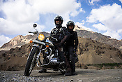Photographers, Sanjit Das and Suzanne Lee (pillion) pose on their Enfield motorcycle on the highway to Ladakh.