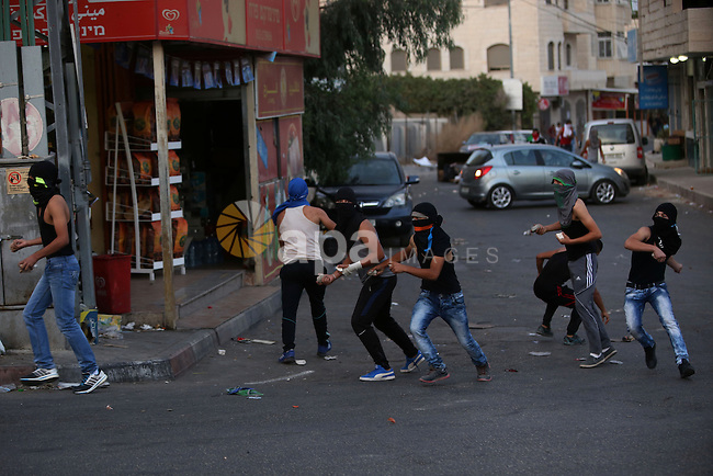 Palestinian protesters throw stones towards Israeli security forces during clashes over the Al-Aqsa mosque compound, close to the Israeli manned checkpoint of Hezma in the Israeli occupied West Bank, between Jerusalem and and the Palestinian city of Ramallah on September 30, 2015. The compound has been the scene of repeated clashes in recent weeks, provoking international calls for calm at the highly sensitive site which is the third holiest in Islam but is also known to Jews as the Temple Mount, the most sacred in Judaism. Photo by Shadi Hatem