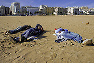 Moroccan Haraga refugees sleep on the beach of Tanger, after a busy night when they were trying to get illegaly inside the port and escape from Morocco, 23 October 2006. Every day tens of Moroccan young men try to cross ilegally the Strait of Gibraltar. ?Harraga? (immigrants in Arabic) come to Tanger from all over Morocco. They try their good luck and hidden between the wheels of a truck they attempt to board on a ferry and get to Spain, eventually further to Europe. Considering the thorough checks at the port only few of them make it. Therefore they spend months living on a beach, in huts along the walls of the port, begging for food and waiting for the right night so as their dream about Europe came true.