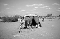 A family standing in front of their makeshift shelter in the Dadaab refugee camp in Kenya. The drought is the worst in East Africa for 60 years. The UN described it as a humanitarian emergency. The already overcrowded complex received 1,000 new refugees a day in June, five times more than a year ago. About 30,000 people arrived at the Dadaab refugee camp in June, according to UNHCR compared to 6,000 in June 2010.