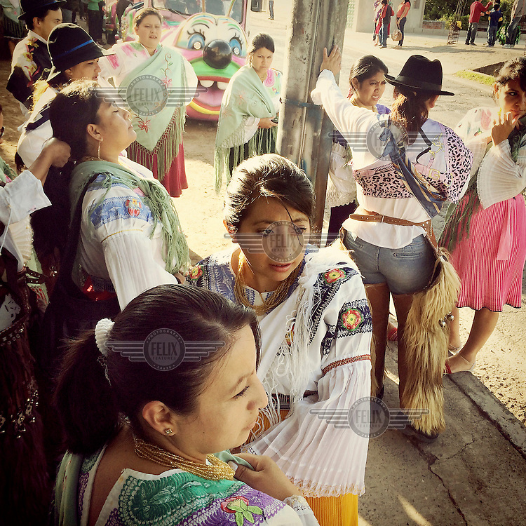Teachers and parents of children from a local school prepare to dance in the street for the fiestas of Tumbaco. They are wearing traditional clothing from Cayambe.